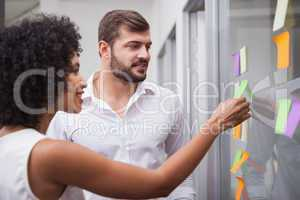 Casual business team looking at sticky notes