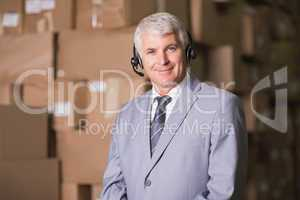 Businessman using headset in warehouse