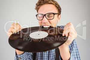 Geeky hipster biting vinyl record