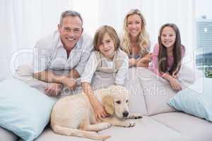 Puppy lying on the couch with the family standing behind
