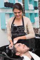 Hair stylist washing mans hair