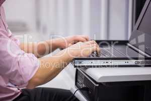 Close up of technician sitting using laptop to diagnose servers