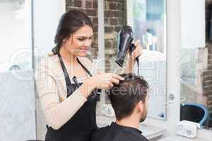 Hair stylist drying mans hair