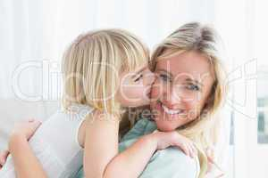 Mother sitting on the couch with her daughter kissing her cheek