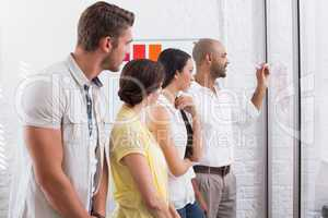 Colleagues watching thinking businessman writing