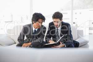 Businessmen sitting on couch together