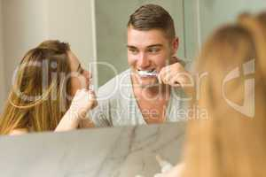 Cute couple brushing their teeth