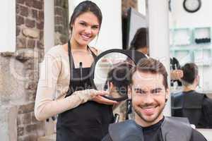 Pretty hair stylist showing man new haircut
