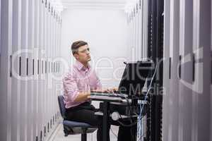 Technician sitting on swivel chair using laptop to diagnose serv