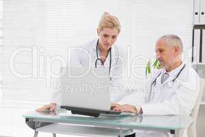 Concentrated doctors coworker using laptop
