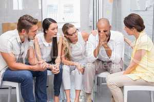 Business team sitting together supporting sad colleague