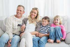Smiling family sitting on sofa changing tv channel