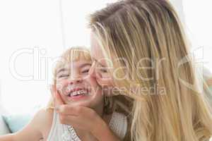 Mother kissing happy daughter on the cheek