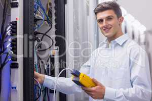 Technician smiling at camera while fixing server