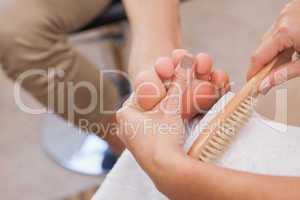 Customer getting pedicure at nail salon