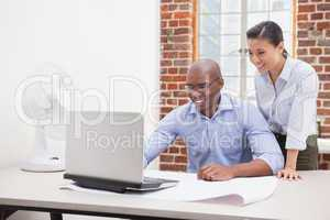 Casual business team using laptop at desk