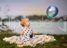 Baby am See mit Luftballon