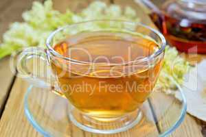 Tea from meadowsweet in glass cup and teapot on board