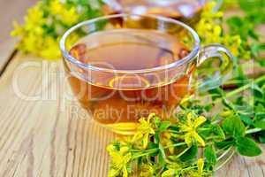 Tea from tutsan in glass cup on board