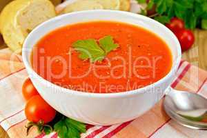Tomato soup in bowl on napkin with bread