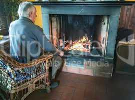 Retired man enjoying home warmth close to fireplace