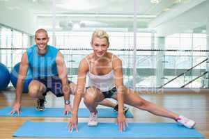 Sporty couple doing pilate exercises at fitness studio