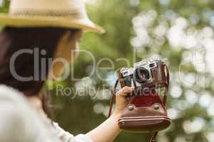 Brunette in straw hat taking a selfie with retro camera