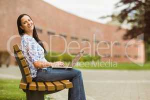 Happy brown hair sitting on bench using laptop