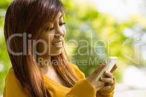 Beautiful woman text messaging in park