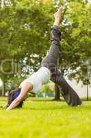 Peaceful brown hair doing yoga on grass
