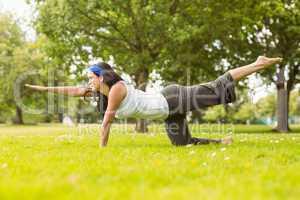 Brunette in balance pose on grass