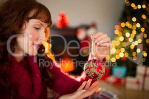 Cheerful redhead holding red bauble