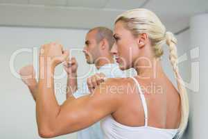 Sporty couple clenching fists at fitness studio