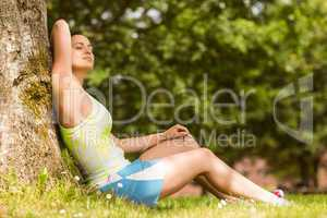 Relaxed fit brunette sitting against a tree