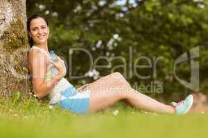 Fit brunette sitting against a tree holding her bottle