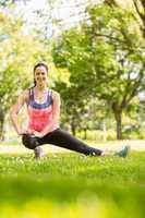 Happy fit brunette stretching on grass