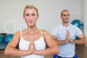 Sporty couple with joined hands at fitness studio