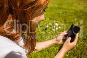 Pretty redhead text messaging on her phone