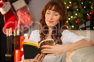 Interested redhead sitting on the floor reading