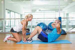 Trainer assisting young man with abdominal crunches at fitness s