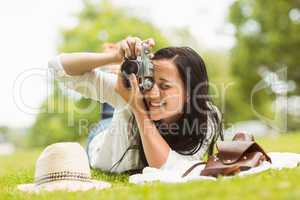 Happy brunette lying on grass taking picture