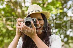 Smiling brunette in straw hat taking picture