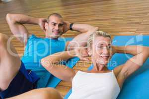 Sporty couple doing abdominal crunches at fitness studio
