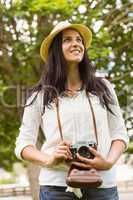 Smiling brunette holding old fashioned camera