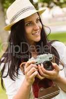Happy brunette in straw hat holding retro camera