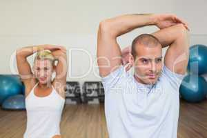 Couple stretching hands behind back in yoga class
