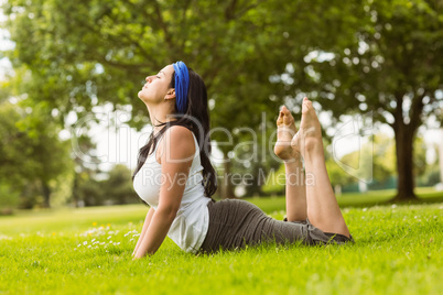 Calm brown hair doing yoga on grass