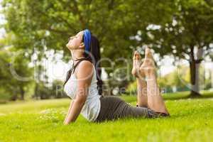 Calm brown hair doing yoga on grass