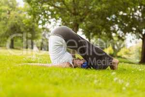 Brown hair doing yoga on grass