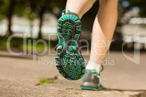 Woman in running shoes jogging on path